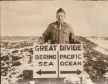 Clifford McGinnis and a sign illustrating the Bering Sea and Pacific Ocean
