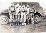 Servicemen (Mel is second from right) and a Jeep