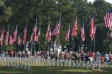 Volunteers gather to begin placing flags on graves in the National Cemetery at Andersonville National Historic Site