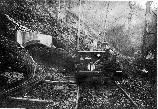 A motor car pulling tram cars loaded with coal exits a mine near Blue Heron.