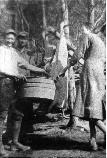 This 1919 photograph shows (left to right) Will J. Miller, Harve Slaven and Ellen Miller slaughtering a hog on their farm in the No Business Community.