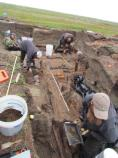 Scientists remove loose soil from an old pit house.