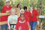 A group of Coca Cola employees with their kids after completing a fence with their VIP Trail Blazer Sylvia Talley.