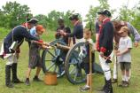 Reenactors teach children the 18th century artillery drill.
