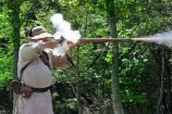 Smoke erupts from the vent, and fire shoots from the muzzle of a flintlock as a militiaman fires.