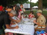 A volunteer looks on as a family signs the Declaration of Independence.