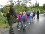 young children walk down a wet pathway in front of a ranger