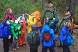 children in brightly colored rain jackets and two rangers look upward and catch raindrops in their open mouths