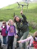 a ranger holds up a radio tracking tool while talking to children