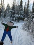 paper cutout of a boy, in front of a ski trail through a snowy forest