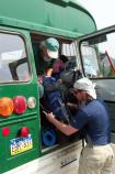 bus driver helps visitor place gear into the back of a green shuttle bus