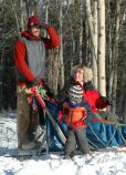 woman and small child receiving a dog sled ride
