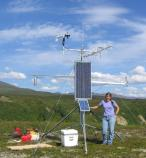woman standing near a tall weather station in front of a background of green hills
