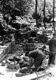 Historic photo of 3 men building stone walls for fish rearing ponds