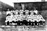 Historic photo of men from a baseball team posing for a photo in their baseball uniforms.