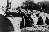 View of workers building the Elkmont Bridge taken from the bank of the river.