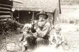 A bearded elderly man playing a fife for is two young grandchildren