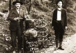 Historic photo of two men standing beside a moonshine still