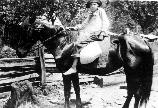 Historic photo of a young boy on horseback holding a sack of corn
