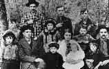 Historic photo of a family with many children. The men in the back row are holding guns.