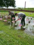 Rangers Kathryn Harrison and Matt Boswell placing flags on grave sites at the Chalmette National Cemetery.