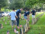 Image of men putting flags at headstones in national cemetery