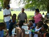 A ranger assists Boys and Girls Club staff with serving snacks.