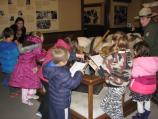 Young students look at a museum display with a ranger explaining the exhibit