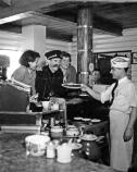 Martin Itjen and two women lean over a diner counter to receive a plate from a server