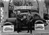 Photo of Martin Itjen shaking hands with O.L. Cowen in front of a Ford V-8 car