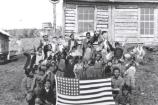 black and white image of around twenty children holding up an American flag