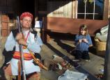 Reenactor portraying Cherokee Indian and girl making beads.