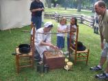 Kids learn Colonial candle dipping