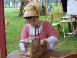 Young reenactor learns weaving.