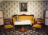 A formal sitting area with yellow chairs and settee, a table with a samovar and tea cups, and a portrait of the czar.