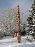 Black and red totem pole in the snow.