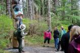 A ranger stands in front of a totem pole on the Totem Trail and talks to visitors.