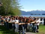 Many members of the Sitka community hold logs that support a totem pole as they walk to the destination.