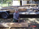 Preservation team member hews sill beam for kitchen house.