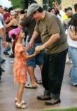 A father and daughter enjoy a dance during the outdoor concert.