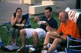A small group enjoys good food while listening to the outdoor concert.