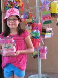 A Junior Ranger adds her own piñata to the piñata tree. The tree is part of a piñata exhibition in the gallery.