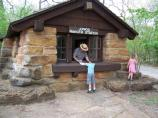 A park ranger talking to a young boy through the window of the Junior Ranger Station.