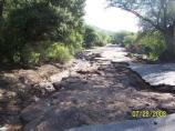Road damage to Montezuma Canyon Rd. includes torn asphalt and erosion of the road bed.