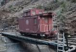 Caboose being pulled across bridge.