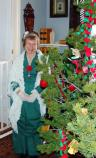 A living history volunteer poses next to the Christmas tree installed in the Commanding Officer's Quarters.