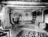 UPSTAIRS SALES ROOM IN HOPI HOUSE. BENCHES AROUND ROOM DRAPED WITH NAVAJO RUGS. CIRCA 1905. DETROIT PHOTOGRAPH