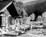 3 VISITORS SIT OUTSIDE ORIGINAL LODGE AT PHANTOM RANCH. VIEW TO S. SMALL COTTONWOOD TREES. CIRCA 1925. KEYSTONE STEREOVIEW CO.