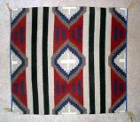 Navajo Rug, Third Phase Chief design. Colors are primarilly red, blue, white, and gray. Often square. Triangles in the corners and a diamond in the center. Striped without a border.