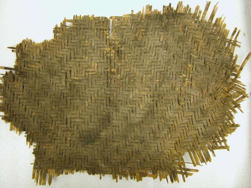 """Image: a yellow-brown woven mat in which the """"threads"""" are flat plant fibers."""